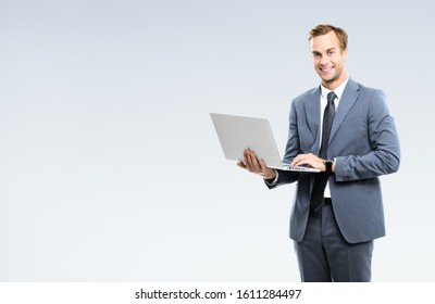 Happy smiling businessman in grey confident suit, working with laptop, with copy space for some slogan or text. Success in business concept.