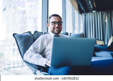 Happy smiling businessman having online conference via laptop computer sitting in office chair, cheerful male employer in spectacles having video call via notebook connected to company wifi internet