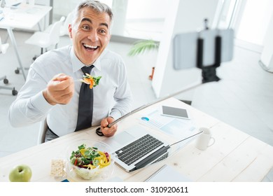 Happy smiling businessman at office desk having a lunch break and taking selfies with a selfie stick and a smart phone