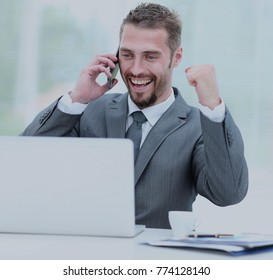 Happy smiling businessman working with laptop and calling.