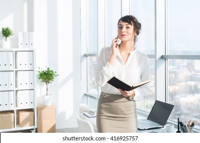 Happy smiling businesswoman having a business call, discussing meetings, planning her work day, using smartphone.