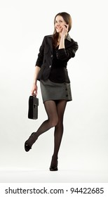 Happy smiling businesswoman speaking on the mobile phone holding briefcase; full length portrait on neutral background