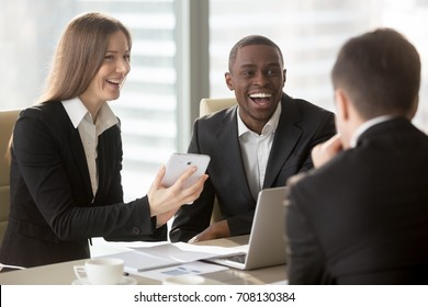 Happy smiling caucasian businesswoman using digital tablet at negotiations with multinational partners, laughing at joke on meeting. Friendly atmosphere on interview, successful teamwork in business