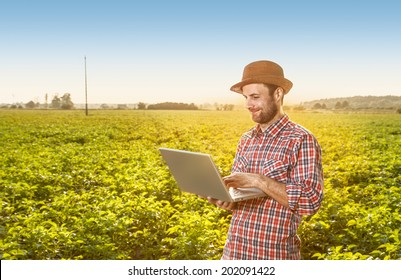 Happy smiling caucasian forty years old modern farmer in a hat standing outdoor in front of field landscape and working on laptop computer - agriculture. Layout with free text space.