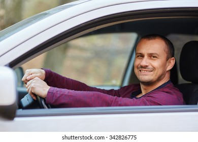 Happy smiling caucasian man with his new car