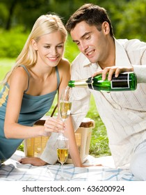 Happy smiling cheerful attractive young couple with champagne at picnic, outdoor. Love and relationships concept.