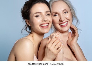 Happy smiling cheerful excited satisfied grey-haired senior mother and brunette young daughter holding hand and hugging with love tenderness closeup studio portrait. Different age generation bonding