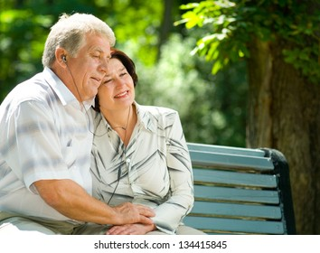 Happy smiling cheerful senior couple listening music or audio book in headset or praying together, outdoors