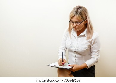 Happy smiling cheerful young businesswoman writing on clipboard, isolated on white background