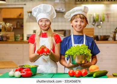 Happy smiling Chef boy and girl preparing healthy food at kitchen. the concept of vegetarianism