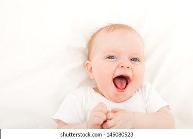 happy smiling child with blue eyes lying in bed over white