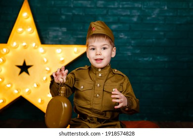 Happy smiling child boy in military uniform. Young soldier. Little patriot. Army thee kid. Boy playing soldier. Portrait of happy young boy in camouflage. Military and rescue operation concept.