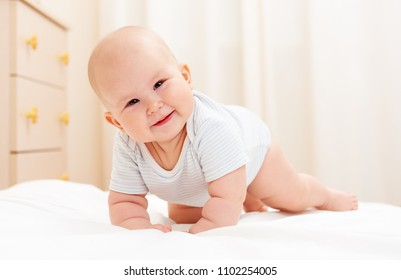 Happy smiling child crawling on the bed at home. Baby care concept.