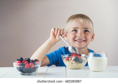 Happy, smiling child eating oatmeal with berries. The concept of a healthy breakfast for children, porridge with raspberries and blackberries, a glass of yogurt on white wooden table.