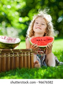Happy smiling child eating watermelon outdoors in spring park