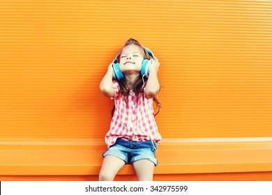 Happy smiling child enjoys listens to music in headphones over orange background