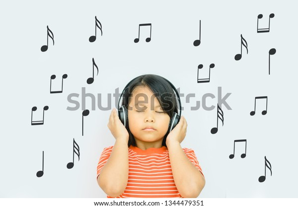 Happy smiling child enjoys listens to music in headphones and close eyes at home.Happy Asian girl enjoy to listening kid song.Relax, listen music concept.