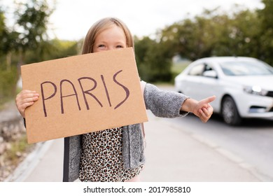 Happy smiling child girl 3-4 year old hold paper craft Paris handwritten sign hitch hiking on road outdoors. Happiness. Little kid toddler travel wear casual clothes and backpack. Summer vacation time