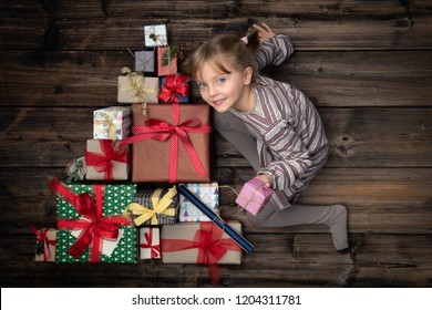 Happy smiling child girl in homewear keeping gift in vertical top view vintage wood with christmas tree pine made of gifts present boxes.Xmas winter holiday season party social media card background