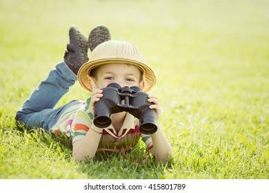 happy smiling child with hat play with binoculars in a garden