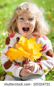 Happy smiling child holding yellow maple leaves in autumn park