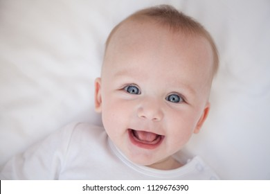 happy smiling child lies on his back on a white sheet