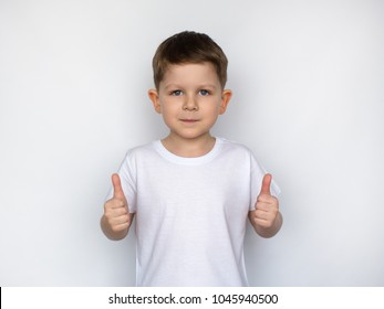 Happy  smiling child, little boy showing thumbs up gesture in a white T-shirt isolated on white background. Space for Your Text. Ok sign