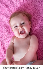 happy smiling child lying in bed over pink