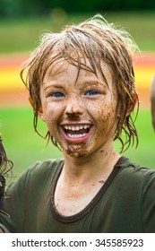 Happy, smiling child with muddy face after sport