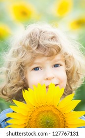Happy smiling child with sunflower in spring field