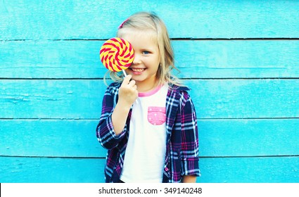 Happy smiling child with sweet lollipop having fun over colorful blue background