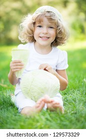 Happy smiling child with vegetables sitting on grass outdoors in spring park against green blurred background. Healthy eating concept