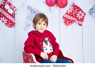 Happy smiling child in a winter sweater riding sledge. Christmas time concept