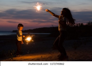 happy smiling children with Sparklers on the beach at night. New Year, Christmas, holiday, birthday, concept.