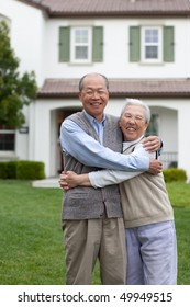 Happy Smiling Chinese Elderly Couple Standing in front of New House Hugging