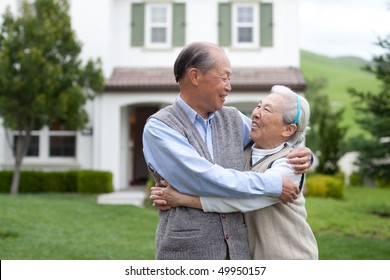 Happy Smiling Chinese Elderly Couple Standing in front of New House