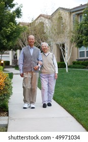 Happy Smiling Chinese Elderly Couple Walking in Residential Community