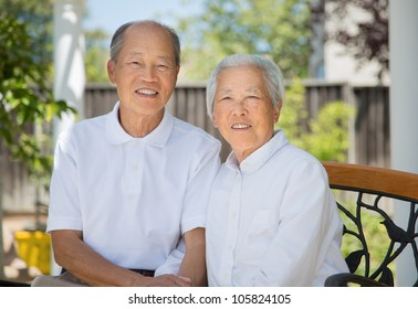 Happy Smiling Chinese Elderly Sitting on Garden Chair Backyard