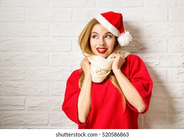 Happy Smiling Christmas Girl in Red Winter Clothes at White Brick Wall Background. Winter Woman Fashion Portrait. Beautiful Female Teenage. Copy Space.