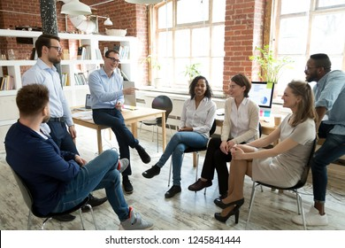Happy smiling coach, tutor, boss laughing at female employee joke at briefing, colleagues having fun together at company meeting, multiracial staff, team building training relationship in team concept
