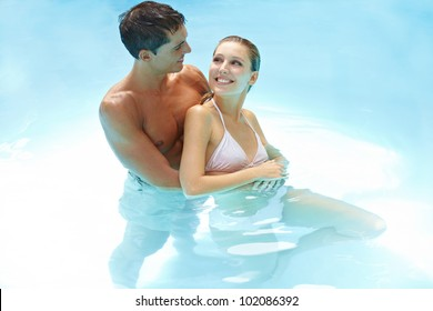 Happy smiling couple bathing together in swimming pool