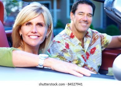 Happy smiling couple in a convertible car. People outdoors.