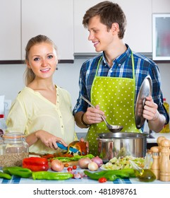 Happy smiling couple cooking vegetables together at home kitchen