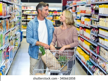 Happy smiling couple doing shopping at supermarket
