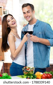 Happy smiling couple drinking redwine, at home. Portrait image of models with red wine glasses in love concept. Happy man and woman posing together indoors.