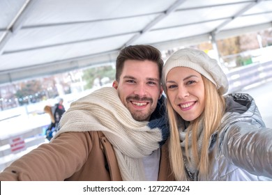 Happy smiling couple having fun on the ice rink while making selfie photo and spending time together