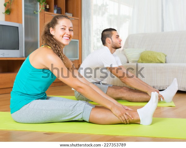 Happy smiling couple having yoga class at home. Focus on girl