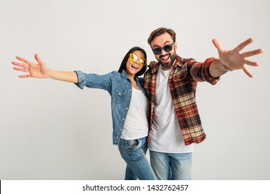 happy smiling couple holding hands in camera isolated on white studio background, stylish man and woman in casual denim outfit wearing shirt and sunglasses having fun together, dating friends