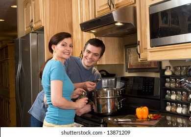 Happy, smiling couple in the kitchen near a counter, microwave, and a chopped pepper. He is about to taste the food she is cooking on the stove.  Horizontally framed photograph