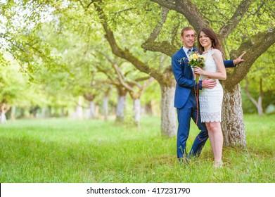 Happy Smiling Couple in love in orchard, spring